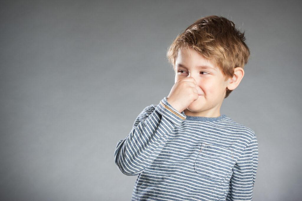 H2S smells bad - Illustration image of little boy holding his nose.